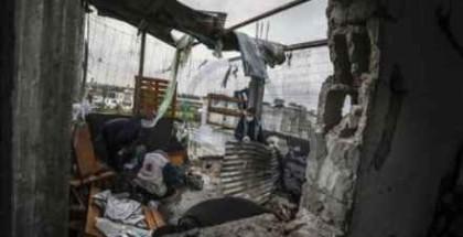أسرة فلسطينية تتفقد أطلال منزلها الذي دمرته طائرات الاحتلال في غزة