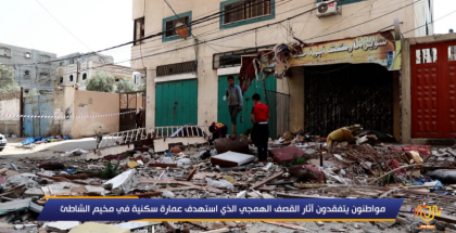 مواطنون يتفقدون آثار القصف الهمجي الذي استهدف عمارة سكنية في مخيم الشاطئ