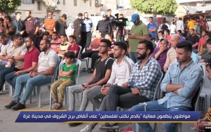 الفلسطينيون يشاركون في حدث بالدم نكتب لفلسطين بالقرب من أنقاض برج الشروق الذي دمرته الغارات الجوية